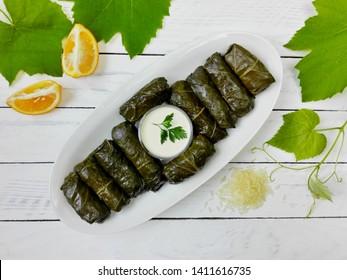 Delicious dolma (sarma) stuffed grape leaves & rice, white yogurt sauce. Lebanese dolma sarma on plate. Lebanon turkish greek middle eastern cuisine. Dinner food dolmadakia or dolma. Yaprak sarma