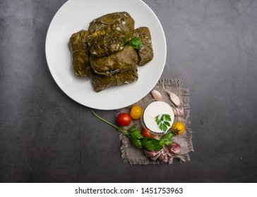 Delicious dolma sarma stuffed grape leaves rice, white yogurt sauce. Lebanese dolma sarma on plate