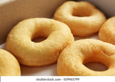Delicious donuts in a cardboard box, closeup