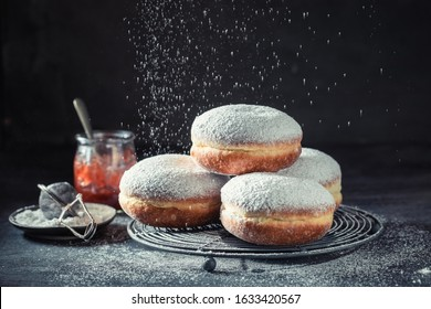 Delicious donuts with powdered sugar on dark table