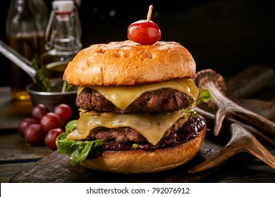 Delicious double venison cheeseburger with olives and melting cheese on a toasted crusty bun served on a rustic wooden table alongside deer antlers