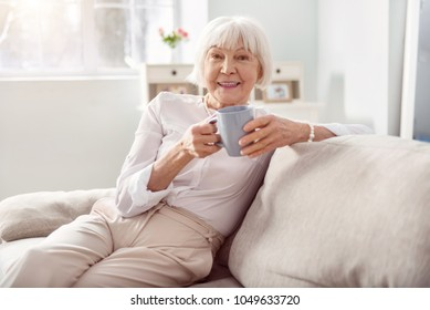 Delicious drink. Cheerful elderly woman sitting on the sofa in her living room and holding a cup of coffee while smiling at the camera