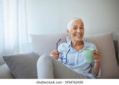 Delicious drink. Cheerful elderly woman sitting on the sofa in her living room and holding a cup of coffee while smiling at the camera. Happy beautiful dreamy old senior middle aged woman sit on sofa
