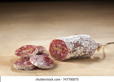 Delicious dry sausage with walnuts on wood
