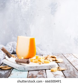 Delicious dutch gouda cheese with cheese blocks, crackers and special knife on old wooden table.