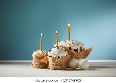 delicious easter cakes with candles and chicken eggs on turquoise