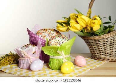 Delicious Easter cakes, dyed eggs and basket with flowers on wooden table