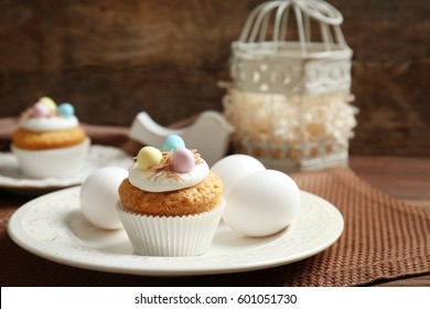 Delicious Easter cupcake on white plate against wooden background