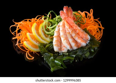 Delicious Ebi Sashimi (Sweet Shrimp, Prawns) with carrot, cucumber, nori, lemon on black background. Traditional Japanese cuisine