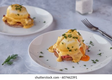 Delicious eggs benedict with bacon, hollandaise sauce and herbs.