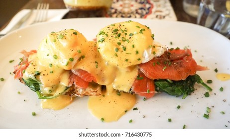A delicious eggs benedict with smoked salmon, hollandaise sauce, and chives on a white plate.