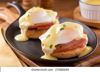 A delicious eggs benedict with thick cut ham, hollandaise sauce, and thyme garnish.