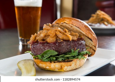 Delicious Elk Burger and Beer served on a white plate with a pickle