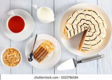 delicious esterhazy torte and a slice of cake on plate with dessert spoon. cup of tea and jug with cream on white table, authentic recipe, hungarian and austrian dessert, view from above