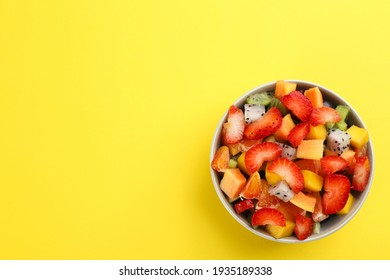 Delicious exotic fruit salad on yellow background, top view. Space for text