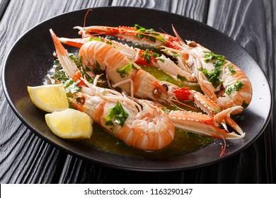 Delicious expensive food. langoustine, scampi with lemon and melted butter with parsley and garlic close-up on a plate on a black table. horizontal