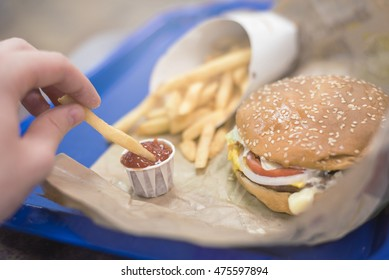 delicious fast food close up, with fries and burger. Hand dipping into ketchup sauce.