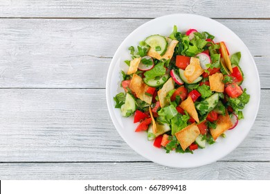 delicious Fattoush or Arab salad with pita croutons, fresh vegetables and herbs,  on white plate on wooden table,  Middle Eastern bread salad. easy and healthy authentic recipe, view from above