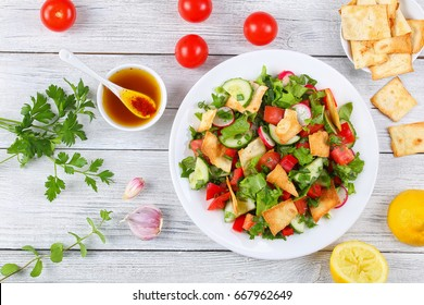 delicious Fattoush or bread salad with pita croutons, fresh vegetables and herbs,  on white plate on wooden table with sumac, lemon, olive oil gravy, authentic recipe, view from above, close-up