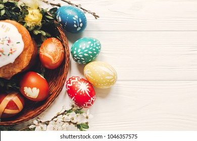Delicious festive bread near willow and easter eggs in basket with leaves and chick toy, Easter celebration concept, flat lay view of easter eggs and kulich, festive food on white wood background