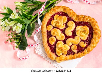 Delicious festive cake in shape of heart for Valentine's Day, Women's Day, Mother's Day. Homemade yeast dough pie with raspberry jam. Original pastries, creative design