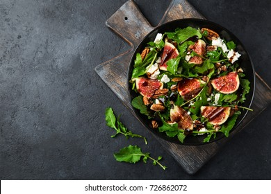 delicious figs, arugula, goat cheese and pecan nuts salad, black background,  top view, copy space