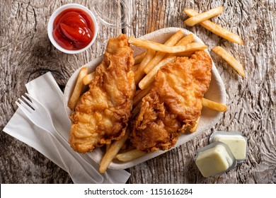 Delicious fish and chips in a take out container with ketchup, tartar sauce, paper napkins and a plastic fork on a rustic wood table top.