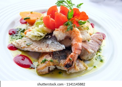 Delicious fish dish from traditional cuisine of Madeira island - grilled fillets of ocean codfish served with shrimps, shells, mussels and celery puree