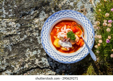 Delicious fish soup outside on the rocks by the sea