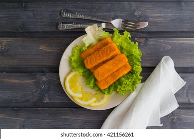 Delicious fish sticks on salad bed with lemon