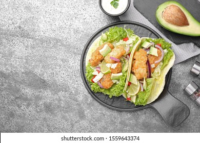 Delicious fish tacos served on grey table, flat lay with space for text
