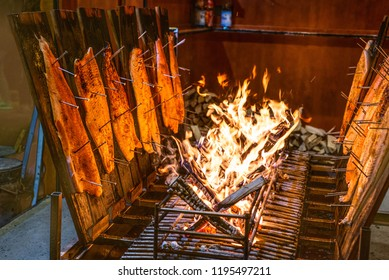 delicious flamed Salmon is smoked on open fire at Christmas market