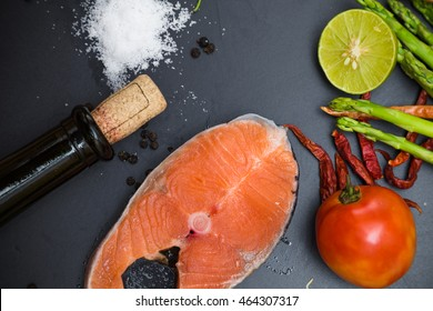 Delicious flat lay of fresh salmon fillet with aromatic herbs and red wine bottle on black plate