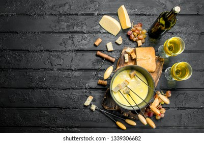 Delicious fondue cheese with white wine. On black rustic background.