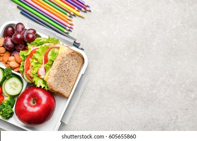 Delicious food and colorful pencils on light textured background