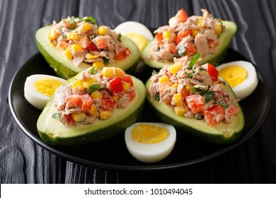 Delicious food: healthy salad of avocado, tuna, eggs and vegetables close-up on a plate on a table. horizontal
