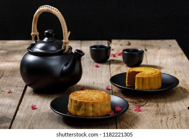 Delicious food moon cake with cup of hot tea on the the wooden table background with copyspace for your text, Chinese traditional festival concept