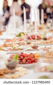 Delicious food ready and decorated.  Banquet table. Table set for banquet with cutlery. Salads, appetizers and glasses with wine.
