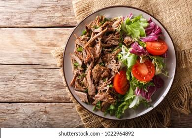 Cuisine délicieuse : viande de boeuf mijotée cuite à la main avec une salade de légumes frais en gros plan sur une assiette. vue de dessus horizontale vue de dessus