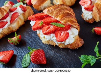 delicious french croissant sandwiches layered with fresh ripe strawberries and whipped cream cheese on a stone tray on a black wooden table, view from above, close-up