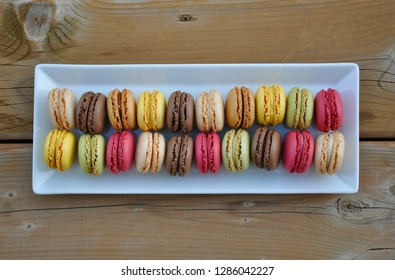 Delicious french macaroons in a white rectangular plate over the wooden table