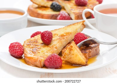 delicious French toast with raspberries and maple syrup for breakfast, horizontal