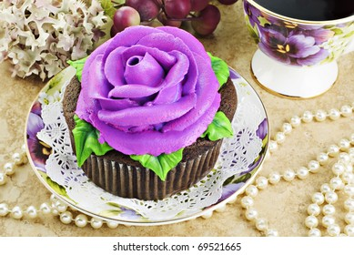 A delicious fresh baked cupcake decorated with a purple frosting rose