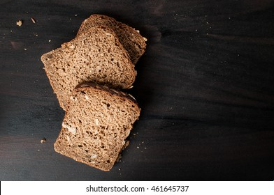 delicious fresh baked slices of bread with sunflower seeds on a dark table photographed from above, horizontal image