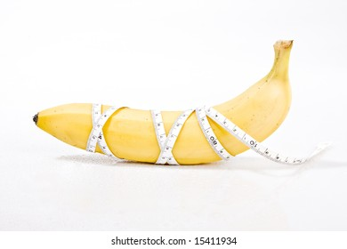 delicious fresh banana on a white surface with a measuring tape wrapped around it. concept: weight loss, diet