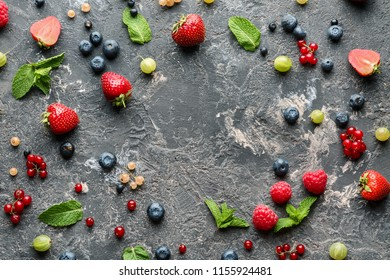 Delicious fresh berries on grey textured background