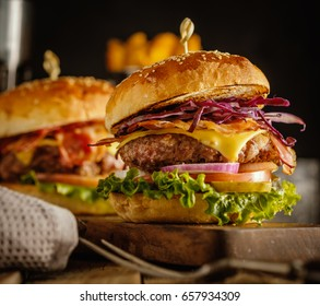 Delicious fresh burger with meat, bacon, cheese and vegetables on a wooden board, in a rustic soul style