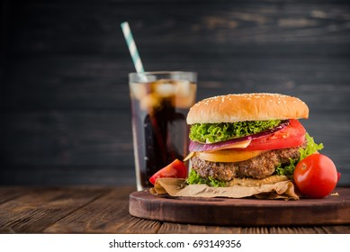 Delicious fresh burger with tomato and cheese and cola glass on background. Fastfood concept dinner