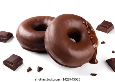 Delicious fresh chocolate donuts with pieces of chocolate on white background. Appetizing tasty glazed donuts ready to eat among pieces of chocolate on white background.