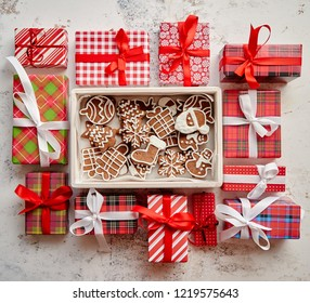 Delicious fresh Christmas decorated gingerbread cookies placed in wooden crate. Wrapped gifts on sides. White rusty background. Top view.
